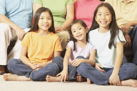 gramma: Three young Asian sisters sitting cross-legged on the floor, San Rafael, California, United States