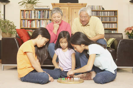 family sofa: Three young Asian sisters playing chinese checkers while grandparents watch, San Rafael, California, United States