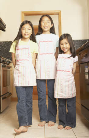domestic kitchen: Three young Asian sisters wearing aprons in the kitchen, San Rafael, California, United States