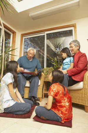 Asian grandfather reading a book to his granddaughters, San Rafael, California, United States Stock Photo - 16090900