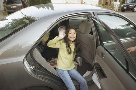 low spirited: Young Asian girl waving from car door, San Rafael, California, United States