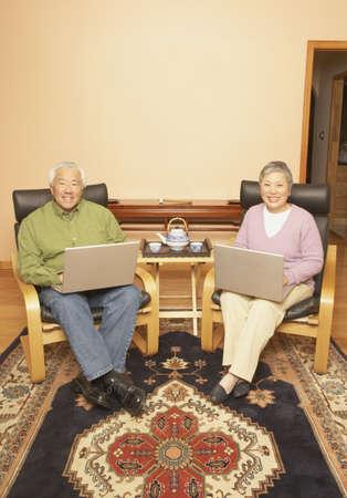 Senior Asian couple having tea while using laptops, San Rafael, California, United States Stock Photo - 16090909