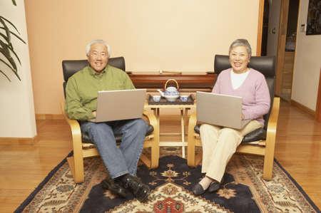 Senior Asian couple having tea while using laptops, San Rafael, California, United States Stock Photo - 16090910