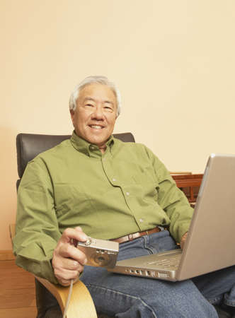 Senior Asian man with laptop and digital camera, San Rafael, California, United States Stock Photo - 16090911