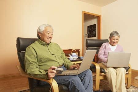 Senior Asian couple having tea while using laptops, San Rafael, California, United States Stock Photo - 16090912
