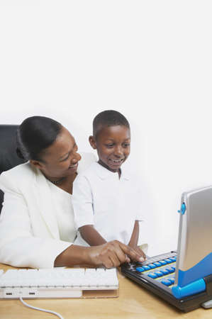 attentiveness: African businesswoman teaching her young son on a computer, San Rafael, California, United States