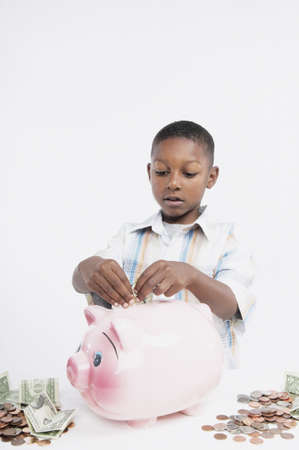 dollarbill: Young African boy putting money in a piggy bank, San Rafael, California, United States