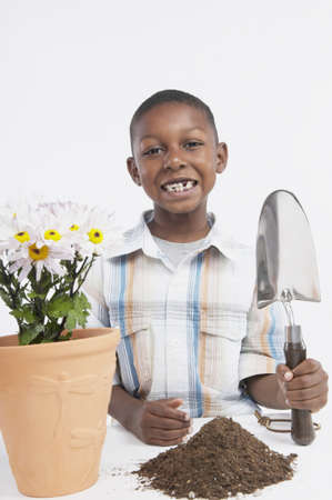 Young African boy potting a plant, San Rafael, California, United States Stock Photo - 16090923