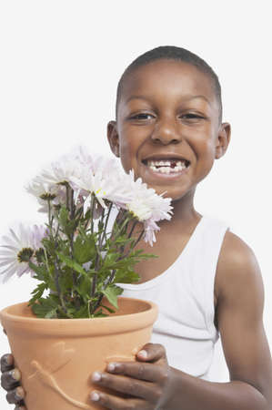 Studio shot of young African boy holding a potted plant, San Rafael, California, United States Stock Photo - 16090924