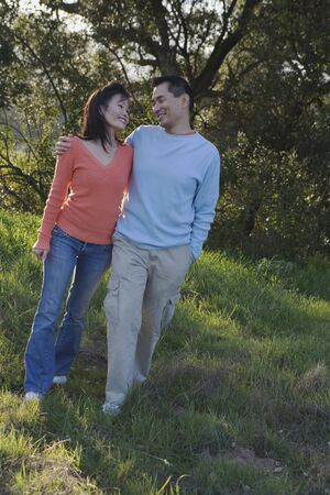 adoring: Asian couple walking in the countryside