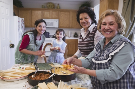 女性ヒスパニック家族食品を準備します。