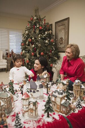 front desk: Hispanic mother and daughter playing with christmas village LANG_EVOIMAGES