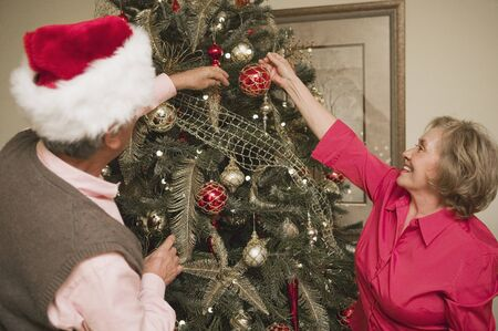 decorating christmas tree: Senior couple decorating a christmas tree