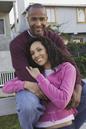 leaning by barrier: African couple hugging