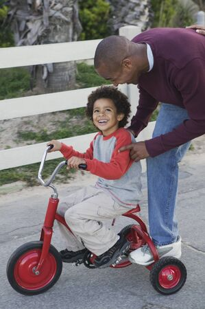 African man helping son on tricycle