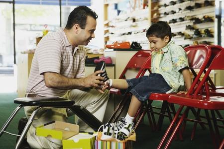 Jonge Spaanse jongen die probeert schoenen bij schoenenwinkel, Port Washington, New York, Verenigde Staten
