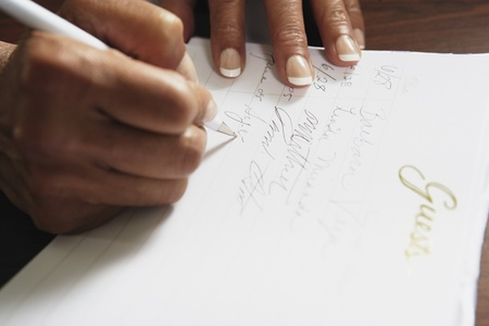 adult  body writing: Woman signing guestbook, Sands Point, New York, United States LANG_EVOIMAGES