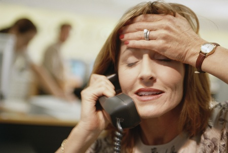 hand on forehead: Businesswoman on telephone with her hand on her head, Dallas, Texas, United States LANG_EVOIMAGES