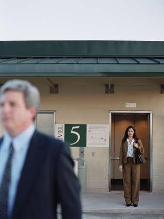 stepping: Businesswomen next to elevator at parking garage, Dallas, Texas, United States