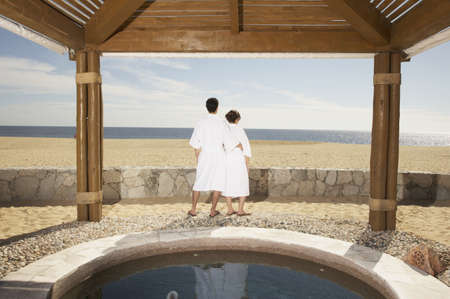 facing away: Couple in bathrobes outdoors at beach resort, Los Cabos, Mexico