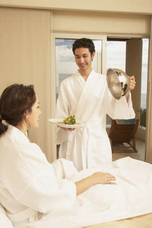 Hispanic couple with food in hotel room, Los Cabos, Mexico Stock Photo - 16090984