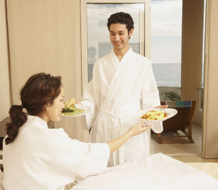 Hispanic couple with plates of food in hotel room, Los Cabos, Mexico Stock Photo - 16090985