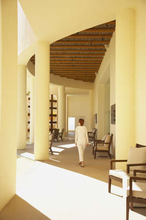 facing away: Woman walking in sunlit lobby of resort hotel, Los Cabos, Mexico LANG_EVOIMAGES