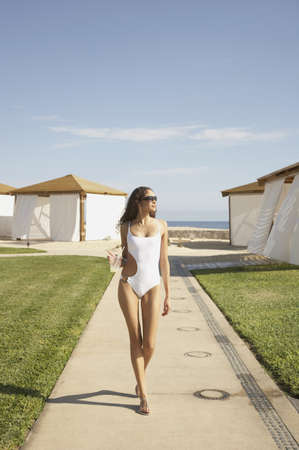 Woman in bathing suit walking with drink at beach resort, Los Cabos, Mexico Stock Photo - 16091001