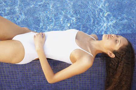 mujer bañandose: Mujer de relax en el borde de la piscina LANG_EVOIMAGES
