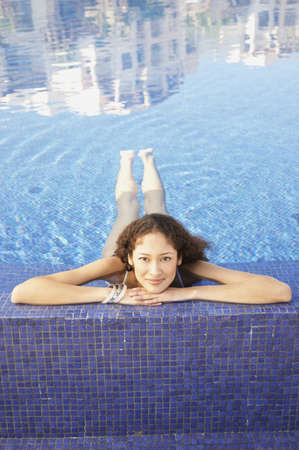 Hispanic woman floating in pool Stock Photo - 16091011