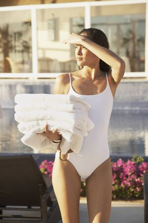 one piece swimsuit: Woman in bathing suit carrying towels