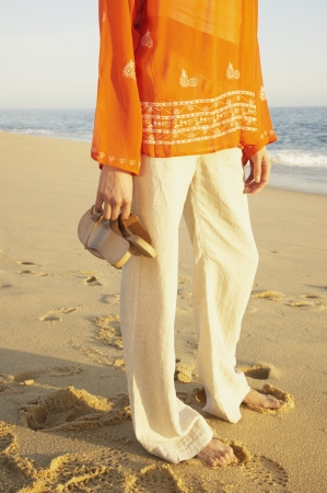 Close up of woman standing on the beach holding her sandals, Los Cabos, Mexico Stock Photo - 16091022