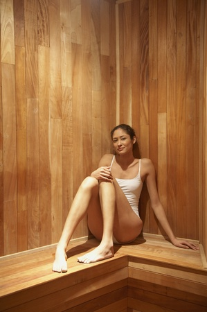one piece swimsuit: Woman sitting in sauna