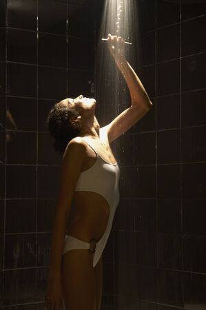 rinsing: Woman in bathing suit rinsing in shower LANG_EVOIMAGES