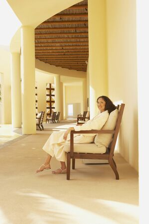 fulfilling: Woman in bathrobe sitting in resort hotel lobby LANG_EVOIMAGES