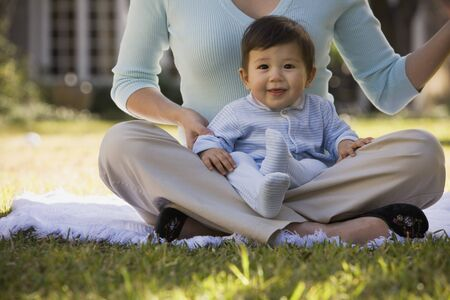 Hispanic baby sitting in mother's lap outdoors Stock Photo - 16091050