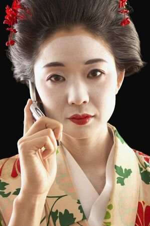 Asian woman in ethnic clothes talking on her cell phone Stock Photo - 16091083