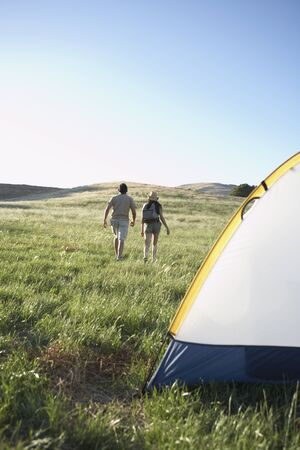 longshot: Young couple walking away from campsite