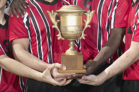 prevailing: Soccer players holding trophy