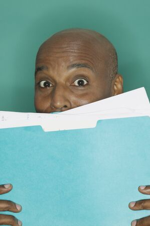 Businessman hiding behind a blue folder Stock Photo - 16091134