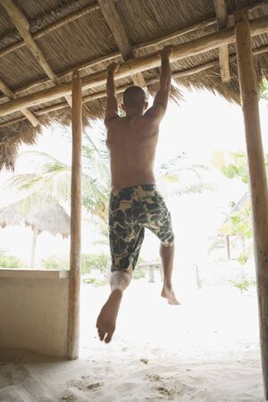 togs: Young man hanging from doorway at the beach LANG_EVOIMAGES