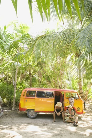 pastimes: People sitting with van in tropical setting