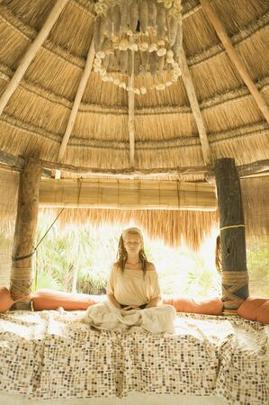 Young woman meditating on bed in hut Stock Photo - 16091170