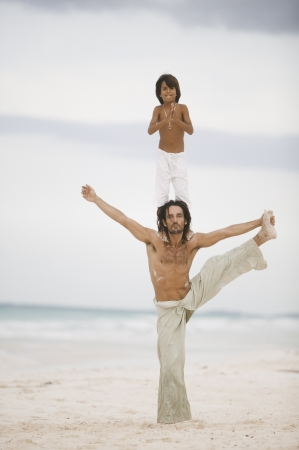 Son standing on his fathers shoulders at the beach Фото со стока