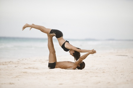 Couple practising gymnastics on the beach