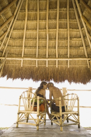 smooching: Couple kissing underneath thatch roof