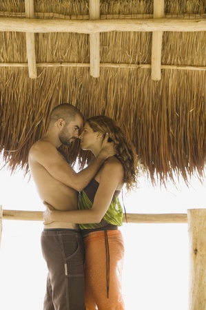 thatch: Couple kissing underneath thatch roof