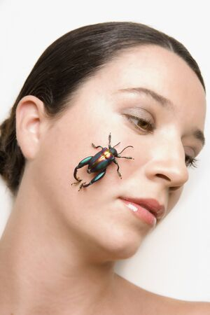 Young woman holding a beetle on her cheek Stock Photo - 16091190