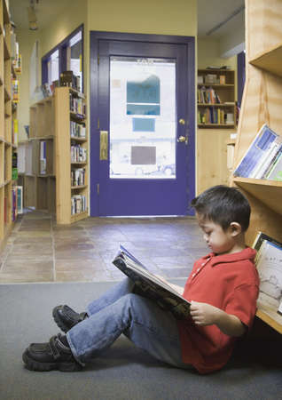 store shelf: Young boy reading book at bookstore LANG_EVOIMAGES