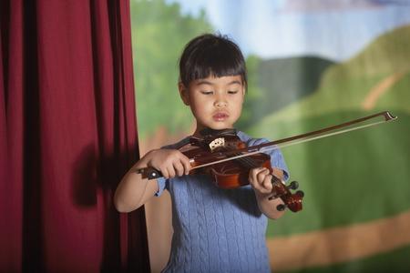 Young Asian girl playing violin at recital Stock Photo - 16091201